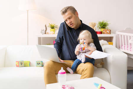 Busy father working with computer while looking after his baby girl 写真素材