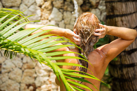 Woman taking outdoor shower in tropics