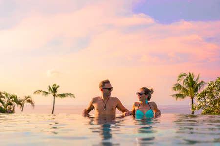 エキゾチックな高級リゾートのインフィニティプールでリラックスカップル 写真素材