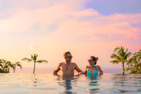 Couple relaxing in infinity pool of exotic luxury resort