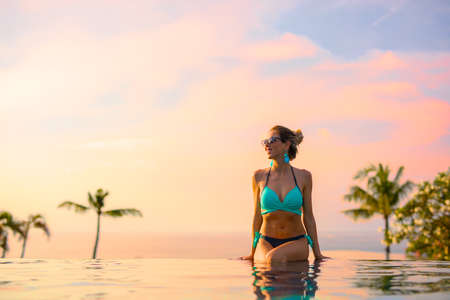 Girl sitting on edge of infinity pool at beautiful sunset