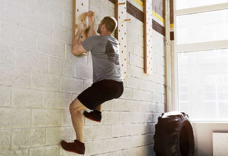 Man exercise on peg board in gym Stock Photo - 91329958