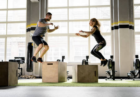 Man and woman jumping on boxes in gym Banco de Imagens