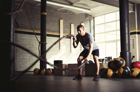 Man with battle ropes in gym Imagens