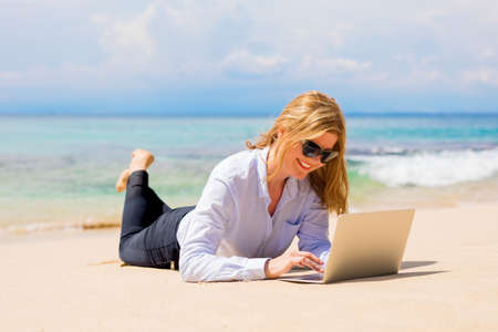 Business woman working with laptop on the beach