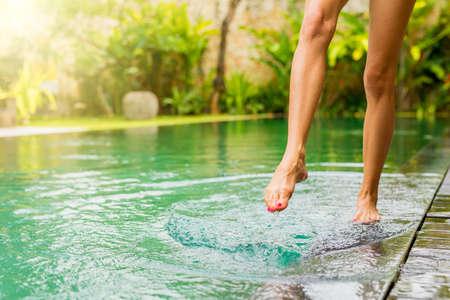 Woman splashing pool water with her leg Stock Photo