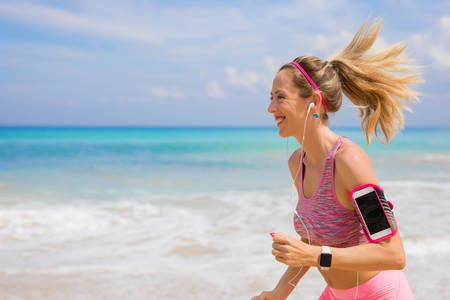 Happy fit girl running on the beach