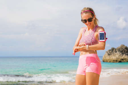 Woman using wearable tech while exercising outdoors
