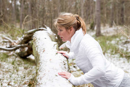 Woman doing push-ups in forest in winter