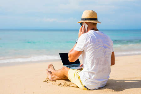 Young man on the beach working with laptop computer and speaking on the phone