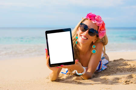 Hipster girl showing empty vertical tablet on the beach, mockup for design.