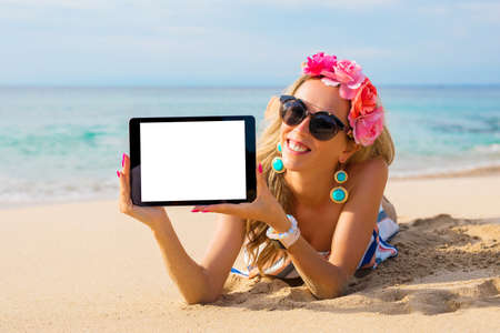 Hipster girl showing empty tablet on the beach, mockup for design.