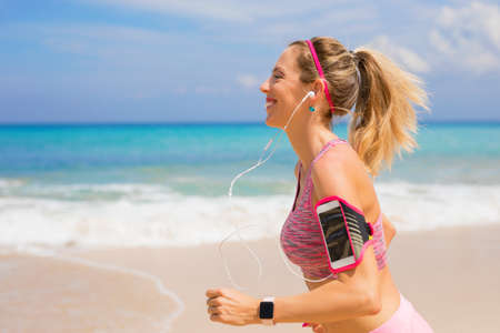 Fitness woman run on the beach Stock Photo