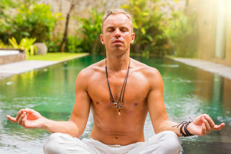 Man meditate by the pool