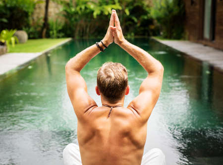 Man practice yoga by the pool Stock Photo