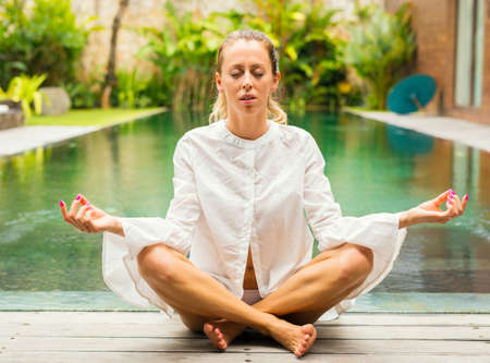 Woman meditate by the pool Stock Photo