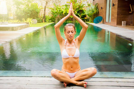 Woman in lotus yoga pose by the pool