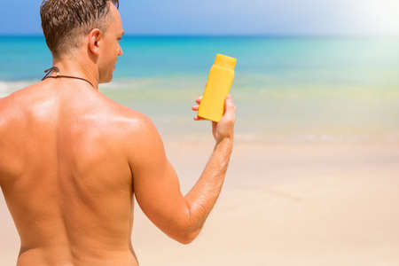 Man sunbathing on the beach and showing sample sunscreen bottle