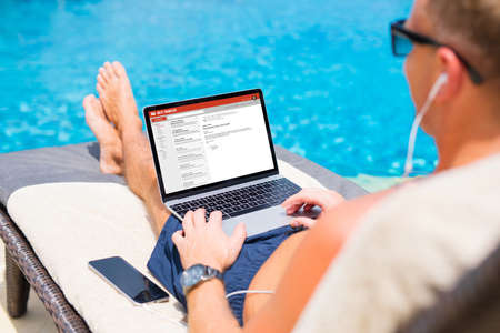 Businessman reading email by the pool Stockfoto