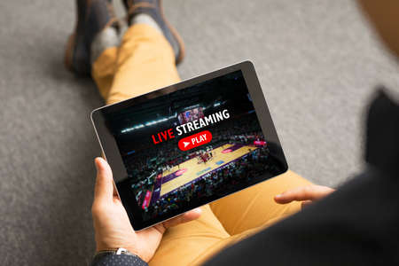 Man watching sports on live streaming online service Foto de archivo
