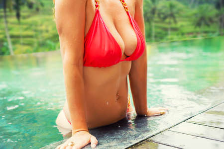 Femme avec de gros seins dans la piscine Banque d'images - 98176194