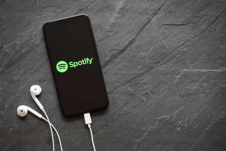 Riga, Latvia - March 25, 2018: Latest generation iPhone X with Spotify logo on the screen.