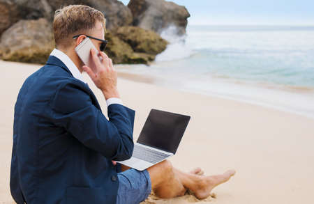 Businessman working on laptop and calling on phone while sitting on the beach Stock Photo