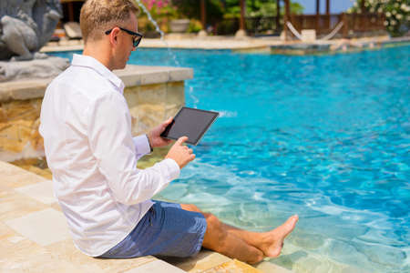 Man using tablet by the pool Stock Photo