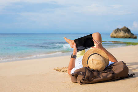 Man lying on the beach and using tablet