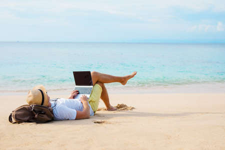 Man working on laptop computer while relaxing on the beach Stock Photo