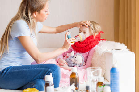 Mom treating sick child with cough Stock Photo