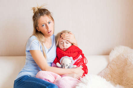 Unhappy mother with sick child at home