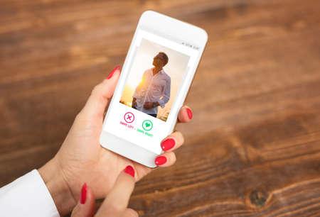 Donna che utilizza l'app di appuntamenti e scorre le foto degli utenti