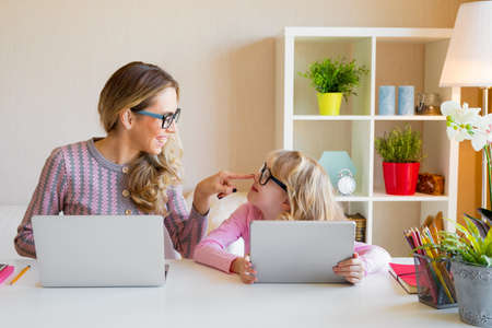 Mother and daughter sitting at table and using computers together Stock Photo