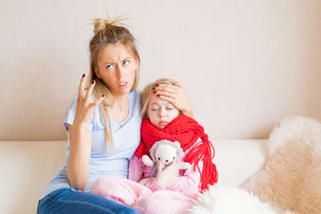 Mother frustrated about her child being sick Stock Photo