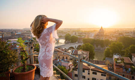 Woman feeling inspired at sunrise on terrace overlooking city Standard-Bild