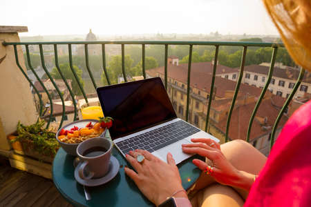 Woman using laptop computer on balcony