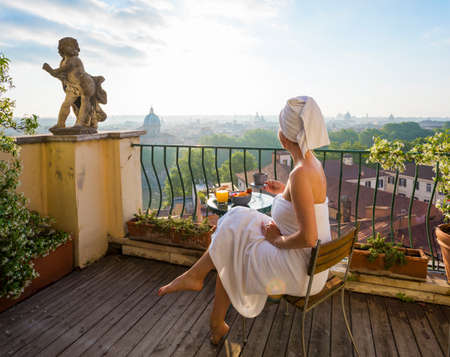 Woman having breakfast on balcony in city