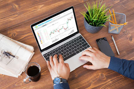 Man trading digital currencies online on laptop computer.