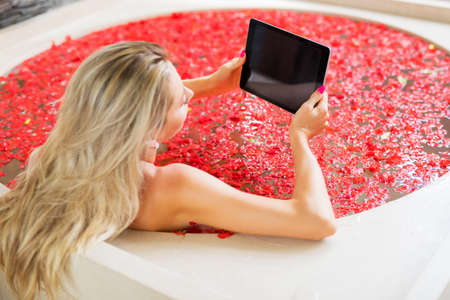 Woman reading on tablet while relaxing in bath Stock Photo
