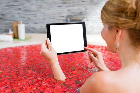 Woman using tablet in red flower bath Stock Photo