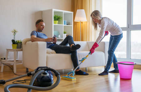 Woman cleaning home and man doesnt help her