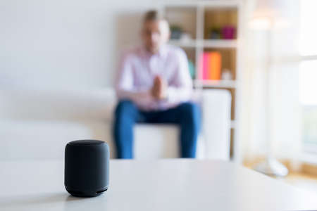 Man talking to virtual assistant smart speaker in living room