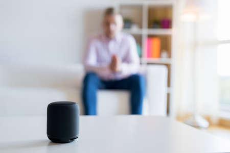 Mann, der mit intelligentem Lautsprecher des virtuellen Assistenten im Wohnzimmer spricht