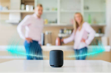 Couple talking and listening to smart speaker at home Фото со стока
