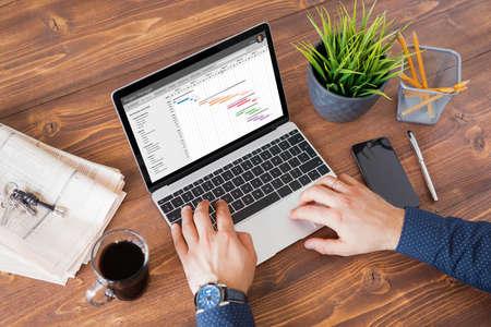 Hombre usando software de gestión de proyectos en el trabajo