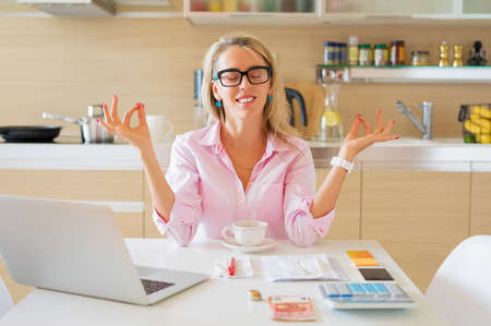 Financially free and calm housewife sitting in kitchen