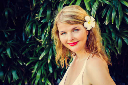 Portrait of woman in front of tropical green foliage. Vintage photo filter applied. Stock fotó