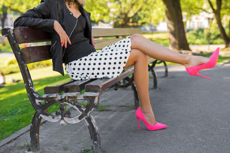 Stylish woman with pink shoes sitting on bench in park