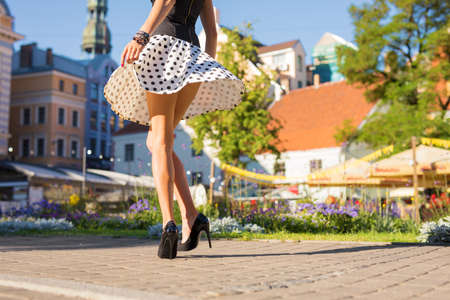 Woman with beautiful legs wearing skirt and heels Фото со стока